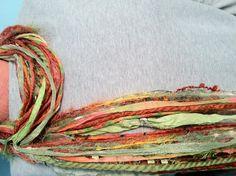 Handmade scarf using yarns, ribbons, and silk.