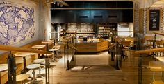 In Starbucks' Amsterdam store, exposed stone walls and repurposed Dutch oak picks up the aged beauty of blue and white Delftware tiles, a local art form dating back to the 16th century, while a cartographic mural celebrates the history of 17th century Dutch coffee traders.