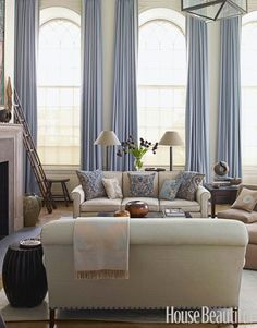 family room, curtains, couches, blue pillows, lamps, bright and light decor