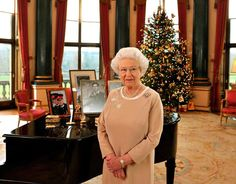 express:  Queen Elizabeth in the Music Room of Buckingham Palace for the Christmas message, 2008; behind her are pictures of her eldest son Prince Charles and her grandsons through Charles and Diana, Princes William and Harry