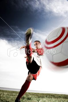 Low angle tilt view of a soccer player kicking the ball in front of a. Low Angle, Soccer Players, Tilt, Image Now, Kicks, Stock Photos, Activities, Football Players