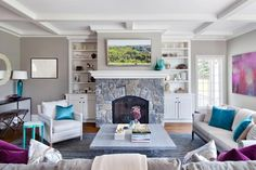 This family room features pale gray accents –– like the wall color and suede sofa –– paired with pops of bright turquoise and deep purple hues. A charcoal and white patterned area rug leads the way to a rustic stone fireplace, finishing the look of the space.