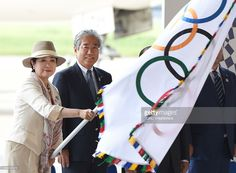 Tokyo Governor Yuriko Koike (L) waves the Olympic flag beside Japan Olympic Committee (JOC) President Tsunekazu Takeda (2nd L) upon its arrival at Haneda Airport in Tokyo on August 24, 2016. The Olympic flag arrived in Tokyo on August 24 as Japan's capital gears up to host the 2020 Games, with officials promising smooth sailing after Rio's sometimes shaky 2016 instalment. / AFP / TORU
