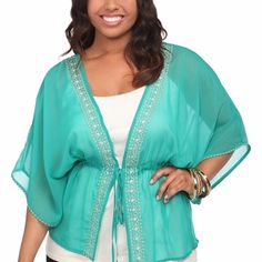 Teal kimono Pretty teal colored kimono. It has cream and tan embroidery on the edges. It's lightweight and sheer. It ties closed in the front. It's marked as 0 in torrid sizes but runs a bit big. It can fit a variety of sizes because of its openness. I'm modeling as a 2x. torrid Tops Blouses