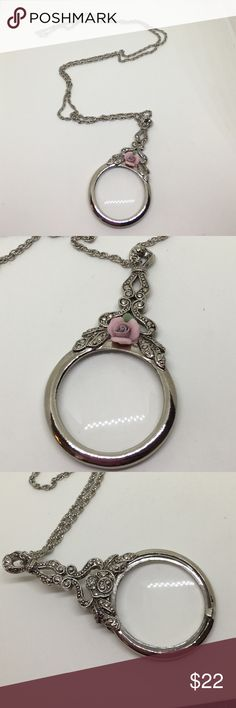 """Hold - Avon Silver Magnifying Glass Necklace A 30"""" silver chain with a 3"""" silver magnifying glass in excellent condition. No scratches are apparent on the glass. The glass setting has faux Marcasites and a ceramic pink rose, giving it a Victorian look; mimicking the reading glasses that ladies of a certain age would use in the library during that era. The glass was slightly loose in the setting and only required a small bit of tightening of a prong, otherwise this piece is in excellent…"""