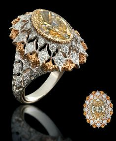 "A RARE COLOURED DIAMOND AND DIAMOND RING, BY BUCCELLATI   The marquise-cut yellow diamond within a fine oval-shaped openwork mount of two-tone stylised snowflake design to the brilliant-cut diamond detail with openwork gallery, shoulders and textured hoop, ring size from 5 to 8 expandable, engraved ""18K""  Engraved Buccellati Italy 18K"