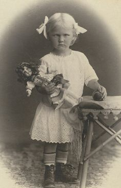 Pouty-faced little girl with a lazy eye holding her doll and a ball  ---  (by sonobugiardo, via Flickr)