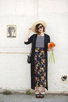 Chapéu de palha, maixi casaco preto, blusa listrada, maxi saia floral, sandália de salto preta