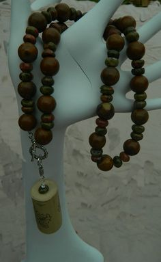 """Pendant necklace, Wine cork hangs from a beautiful jasper chunky bead necklace with rondelle spacers. Front toggle. This is one of my original WINO necklaces. Most definitely will make a statement & be an attention grabber. Shades of brown, green & a hint of pink... Great for clubbing or just for fun. Unique & VERY pretty. From the WINO collection.    Measures...20""""..& cork hangs 3"""" from toggle Chunky Bead Necklaces, Chunky Beads, Beaded Necklace, Pendant Necklace, Wine Cork Jewelry, Cork Ideas, Jasper, December, Jewelry Design"""
