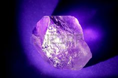Amethyst illuminated from the side ona purple background