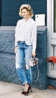 Zanita Whittington wears a button-down blouse, embroidered jeans, lace-up heels, and a graphic mini bag