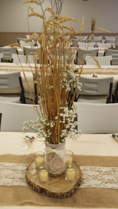 Rustic wheat hay straw wedding centerpiece with baby's breath mixed in. Held in a mason jar covered by an ivory lace doilie. On a woodslab with votives  on a burlap runner with lace