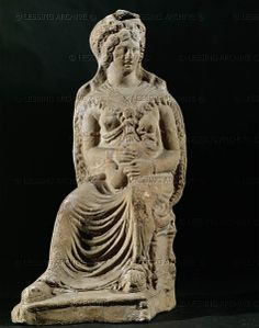 The Goddess Isis nursing the child Horus. This Hellenistic version of the Egyptian goddess Isis wears a fringed cape around her shoulders and vinebranches in her hair. Terracotta (330 BCE-1 CE) from Alexandria, Egypt   Louvre, Departement des Antiquites Grecques/Romaines, Paris, France
