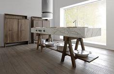 reforma cocina en isla central con encimera de mármol sobre taburetes para fregadero y zona de cocción, armarios auxiliares de madera, suelo de parquet.