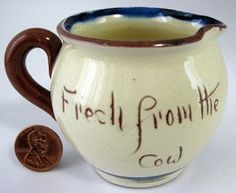This is a Watcombe, Torquay Devon, England mottoware or motto ware pottery creamer, cream pitcher or milk jug in made 1930-1940s. The creamer has the motto Fresh From The Cow with a traditional cottage design, Famous and fun motto ware or mottoware has been manufactured in the south of England from the 1860s until the factories closed in the 1960s.
