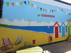 Beach Huts mural painted in a school court yard in Clacton-on-sea, featuring deck chairs, a beach ball and bucket and brightly coloured bunting. This was all hand painted and coated with an anti graffiti varnish.