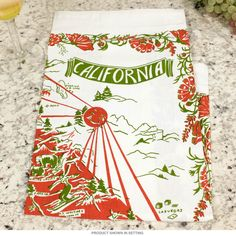 California Red Map Souvenir Flour Sack Cotton Kitchen Towel   Kitchen Linens   RetroPlanet.com Vintage style towel featuring reproduction art paying tribute to your favorite state. Made of 100% machine washable cotton, this high quality linen brings nostalgic regional style to any kitchen!