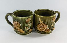 Unique Set of Green earthenware coffee mugs.  Set has a green stripped pattern with yellow daisy's embossed around the cup.  Stack-able.  3 1/4 in height and 4 1/2 in width from edge to handle.   Holds 8 ounces.  No chips or cracks