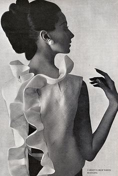 Brigitte Bauer in white silk gazar ruffled jacket worn over a navy-blue faille long dress by Pierre Cardin, photo by William Klein, Vogue US, March 1963