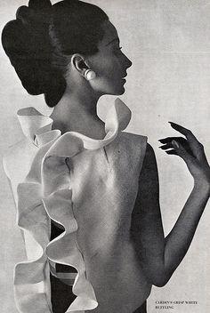Brigitte Bauer in white silk gazar ruffled jacket worn over a navy-blue faille long dress by Pierre Cardin, photo by William Klein, Vogue US, March 1963 @.com