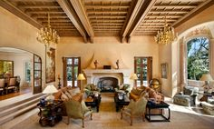 Step down from the salon to the living room with towering layered oak beam and paneled ceiling and two chandeliers; Rumford fireplace with manorial scale stone mantelpiece.  #chandeliers #fireplace