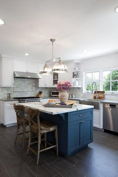 Gorgeous white and blue kitchen features a blue center island accented with a white marble countertop seating two French x-back counter stools on porcelain wood like floor tiles lit by a Restoration Hardware Clemson Classic Double Pendant.