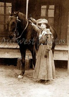 OLD WEST COWGIRL WITH HER HORSE ON A DIRT STREET IN FRONT OF THE BOARDWALK PHOTO