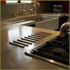 small pic but concrete countertops with built in hot plate & dish drain... it is ridiculous how excited the idea of this makes me... like this color too