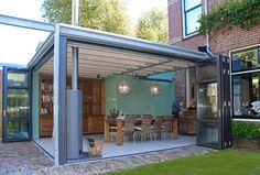 Ontwerp aanbouw / serre met industrial look: stalen frame in het zicht, exposed brick en aluminium glazen harmonicapuien - architect Breda