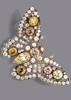COLOURED DIAMOND BUTTERFLY BROOCH. The body and openwork wings collet-set with 7 round diamonds of various fancy colors weighing a total of approximately 6.30 carats, further set with a pear-shaped diamond weighing approximately 1.75 carats, completed by 85 round diamonds weighing approximately 3.20 carats, mounted in gold and silver.