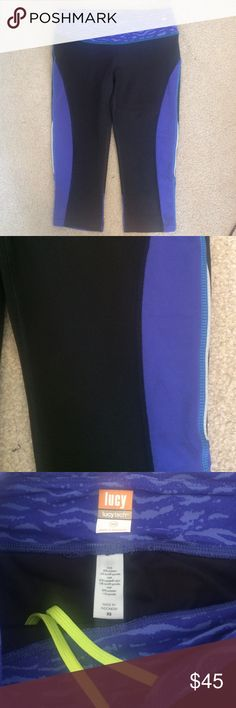 Lucy Cropped Capris Purple Blue Black Leggings XS Lucy Cropped Capris, Size XS, waistband is wavy print, zippered pocket on waistband, black color with purple blue color, reflective strips on sides, in very good condition. Please ask any questions  💲Open To Offers💲 🚫No Trades🚫 📦Ask About Bundle Discounts💰 Lucy Pants Leggings