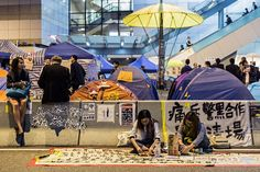 Umbrella Revolution Hong Kong, Pro-democracy protesters and visitors rest along a motorway between two lanes of a blocked main road being used by the Occupy movement in the Admiralty district of Hong Kong on November 20, 2014. Hong Kong police clashed with pro-democracy demonstrators on November 19 after a small group tried to break into the city's legislature, as splits emerged within the movement before the expected clearance of protest camps. AFP PHOTO / ANTHONY WALLACE