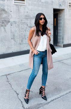 Mulher morena posa para foto de street style usando regata branca, calça jeans skinny azul, colete rosê, scarpin de amarrações preto, bolsa a tiracolo e óculos escuros