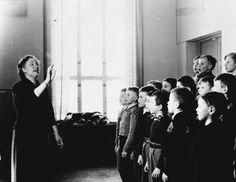 Koulupojat laulavat opettajan johdolla 1940–50-luvulla. Kuva: Helsingin kaupunginmuseo