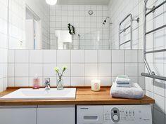 Lavadora en el baño integrada bajo un sobre de madera comun con el lavabo