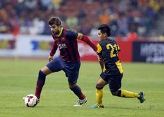 FC Barcelona's Gerard Pique, fights for control of the ball with Malaysia's Mohamad Nazmi Faiz Mansor during the friendly soccer match between FC Barcelona and Malaysia XL in Shah Alam, Malaysia, Satu