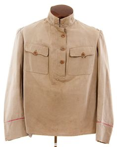 AN IMPERIAL RUSSIAN WWI GUARD OFFICER'S FIELD TUNIC OR GYMNASTIORKA, Model 1907. Khaki cotton pull-over shirt type garment with red cuff piping. Lacks collar insignia and shoulder boards. Buttons on the body are replacements, cuff buttons are original but one is lacking. Scarce combat uniform.  - Jackson's International Auctioneers and Appraisers