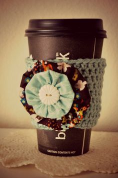 crocheted coffee cozy with fabric embellishment
