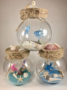 **Fish Bowl Centerpiece Decorations** This unique item features two HANDMADE ORIGAMI RIBBON FISH dangling above an ocean floor of REAL sand and REAL shells! Wow your guests with these beautifully created artistic pieces Bowl is crystal clear plastic (lo Fishbowl Centerpiece, Centerpiece Decorations, Flower Centerpieces, Bottle Decorations, Origami Ribbon, Origami Fish, Unique Wedding Centerpieces, Wedding Decorations, Beach Decorations
