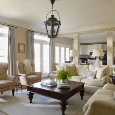 I love the heavy crown molding in this traditional living room & how they added curtains to the french doors