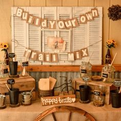Build Your Own Trail Mix Bar. Like the rustic, tiered table display. Banner could be changed to whatever is being served.