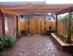 The fence was installed 10 feet in from the alley easement, to make this small backyard feel more open and to maximize the square footage of this project, we moved the fence back and installed a custom gate. In addition, large ornamental trees were installed to screen out the neighbors window. A free standing water feature in the corner can be heard throughout the courtyard and the kitchen.