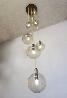 bunch of  tinted glass spheres is with browned brass cylinder designed for a fashion store in austria/ isabel hamm licht 2016