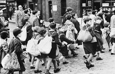 """East End evacuees on their way to the station, 2nd Sept 1939. The problems brought about by the Government Evacuation Scheme were debated in Parliament on 14th Sept 1939: """"It is not surprising that the House of Commons was impelled last night to discuss the problems of evacuation. Certain troubles were bound to follow the dispersal of nearly a million and a half town dwellers, most children and women, into the country and other places of safety..."""""""
