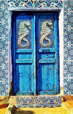 Gorgeous antique vintage turquoise blue door.  Possibly for a beach cottage.  Love the mosaic tile surround.