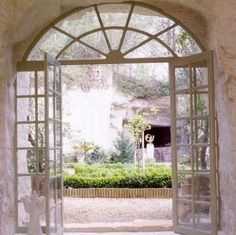 View through the double French windows of the barn into the gravelled courtyard garden - David Hare's Loire valley château French Style Homes, French Country Style, French Country Decorating, French Windows, French Doors, Indoor Barn Doors, French Exterior, Aluminium Doors, Through The Window