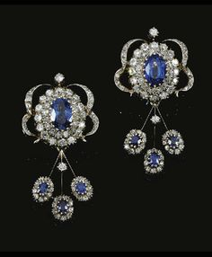 [Earrings] Sapphire and diamond demi-parure,  Mellerio Dits Meller, circa 1870. Necklace designed as a chain of 11 clusters, each set with an oval sapphire within a diamond border  supporting  diamond swags & decorated to the  front with 3 detachable drops,  each set with a sapphire within a border of diamonds surmounted by a diamond ribbon bow motif & supporting 3 sapphire & diamond drops. A pair of matching earrings, mounted in silver and gold. French assay marks