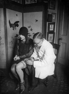 Woman getting a garter belt tattoo.  ca. 1920s.