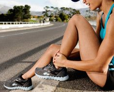 Runner with ankle injury has sprained and strained ankle, painful expression. typical road running p