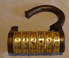 """18th century French combination lock in brass and soft steel. stamped """"Deposee"""" and """"8"""". It has 6 rotating discs rather than the more usual 3 or 4. However each disc also has 16 letters ( letters rather than the more usual numbers), giving the number of possible combinations as 16,777,216  rather than the more usual 4 digit numeral based locks which have a far smaller number of possible combinations of 10,000."""